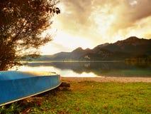 Crogiolo di pagaia capovolto di pesca sulla banca del lago alps Lago autunnale del levelof regolare Fotografie Stock