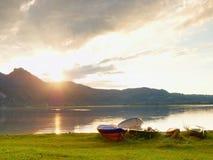 Crogiolo di pagaia di pesca e crogiolo di pagaia capovolto sulla banca del lago alps Immagine Stock