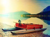 Crogiolo di pagaia di pesca e crogiolo di pagaia capovolto sulla banca del lago alps Ardore del lago morning Immagine Stock Libera da Diritti