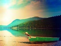 Crogiolo di pagaia di pesca e crogiolo di pagaia capovolto sulla banca del lago alps Ardore del lago morning Fotografie Stock