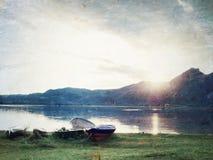 Crogiolo di pagaia di pesca e crogiolo di pagaia capovolto sulla banca del lago alps Ardore del lago morning Immagine Stock