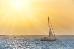 Crogiolo di vela contro il tramonto del mare Fotografie Stock