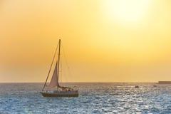 Crogiolo di vela contro il tramonto del mare Immagine Stock