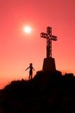 Croisez sur une montagne avec la femme ouverte de bras Photographie stock libre de droits