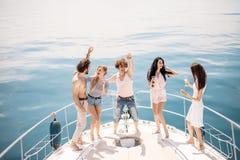 Croisière et vacances marines - jeunes avec des verres de champagne sur le bateau ou le yacht Image stock