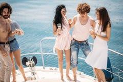 Croisière et vacances marines - jeunes avec des verres de champagne sur le bateau ou le yacht Image libre de droits