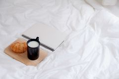 Croissant και βιβλίο στο λειτουργώντας πίνακα το πρωί Στοκ εικόνα με δικαίωμα ελεύθερης χρήσης