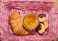 Croissant, μαρμελάδα και μπισκότα σε ένα ρόδινο καλάθι Στοκ Εικόνα