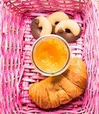 Croissant, μαρμελάδα και μπισκότα σε ένα ρόδινο καλάθι Στοκ Φωτογραφίες