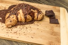 Croissant με τη σοκολάτα σε έναν ξύλινο πίνακα Στοκ Φωτογραφίες