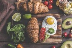 Croissant με το αβοκάντο guacamole, το τηγανισμένες αυγό και την ντομάτα, φύλλα σπανακιού φρέσκος τηγανισμένος χορτοφάγος ντοματώ στοκ φωτογραφίες