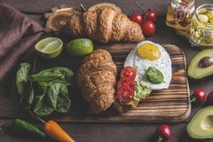 Croissant με το αβοκάντο guacamole, το τηγανισμένες αυγό και την ντομάτα, φύλλα σπανακιού φρέσκος τηγανισμένος χορτοφάγος ντοματώ στοκ φωτογραφία με δικαίωμα ελεύθερης χρήσης
