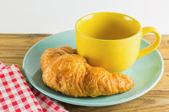 Croissant στο πράσινο πιάτο με το κίτρινο κόκκινο εναλλασσόμενο λευκό καφέ και υφάσματος φλυτζανιών Στοκ Φωτογραφία