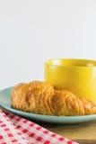 Croissant στο πράσινο πιάτο με το κίτρινο κόκκινο εναλλασσόμενο λευκό καφέ και υφάσματος φλυτζανιών Στοκ εικόνες με δικαίωμα ελεύθερης χρήσης