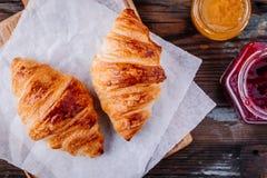 Croissant al forno casalinghi con inceppamento e caffè su fondo rustico di legno fotografia stock libera da diritti