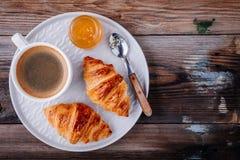 Croissant al forno casalinghi con inceppamento e caffè su fondo rustico di legno fotografie stock