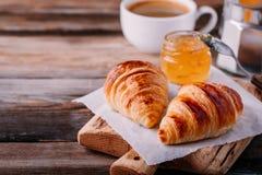 Croissant al forno casalinghi con inceppamento e caffè su fondo rustico di legno immagini stock libere da diritti