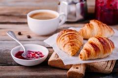 Croissant al forno casalinghi con inceppamento e caffè su fondo rustico di legno immagine stock