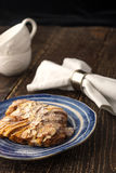 Croissant with almond on the ceramic plate with two blurred cups and napkin Stock Photography