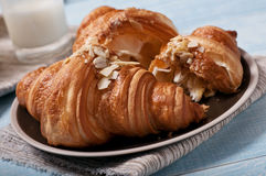 Croissant with almonds on blue wooden surface Stock Images