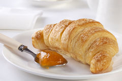 Croissant with Apricot Jam. With white accessories. A beautiful breakfast Royalty Free Stock Photo