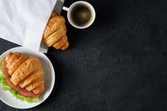 Croissant avec du jambon et la laitue, café sur un fond foncé Image libre de droits