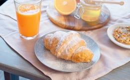 Croissant, barattolo del miele e succo d'arancia sulla tavola di legno Prima colazione sana fotografie stock libere da diritti