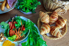 Croissant in basket on wooden table for breakfast. The croissant in basket on wooden table for breakfast stock images