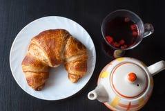 Croissant bavarese fresco e saporito sul piatto bianco e su un vetro del tè della frutta sopra fondo di legno Immagini Stock