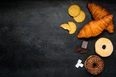 Croissant, biscotti e guarnizioni di gomma piuma sullo spazio della copia Immagine Stock