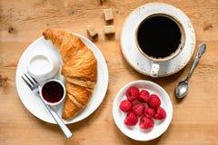 Croissant, black coffee, raspberries and jam on wooden table. Croissant, cup of black coffee, fresh raspberries, cream and jam on wooden table. Continental Stock Photo