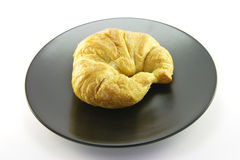 Croissant on a Black Plate Stock Image
