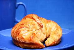 Croissant on blue. Plate and blue background stock photos