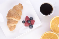 Croissant with blueberries and raspberries on a white plate Stock Image