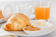 Croissant, boiled egg, freshly squeezed juice, coffee or tea with milk, butter, jam. Continental French breakfast Royalty Free Stock Photo