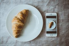 Croissant Bread on Round White Plate Beside Rose Gold Iphone Se Displaying Photo of Croissant Bread on Plate stock photography