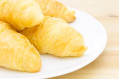 Croissant or Bread on White Dish on Wood Table Royalty Free Stock Images