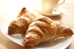 Croissant Breakfast. Croissant and coffee for breakfast, on a wooden table Stock Photography