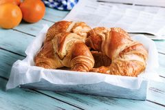 Croissant, orange, newspaper for breakfast on wooden surface stock photos