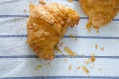Croissant, Brood crump op tafelkleed Stock Afbeeldingen