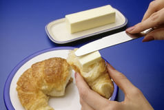 Croissant with butter. Hands buttering a warm breakfast treat Stock Images