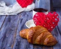 Croissant, café et coeur sur le fond en bois Photographie stock libre de droits