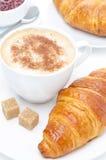 Croissant, cappuccino e doce frescos para o café da manhã, close-up Fotografia de Stock