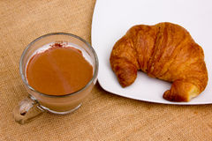 Croissant and cappuccino on placemat Royalty Free Stock Photo