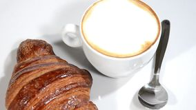 Croissant and cappuccino on a white plate rotating. stock video footage