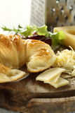 Croissant and cheese. Croissant and emmental swiss cheese, grated and sliced then placed on wooden plate Stock Photo