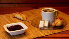 Croissant, cherry marmalade and orange and a cup of coffee on a plate on wooden table stock photo