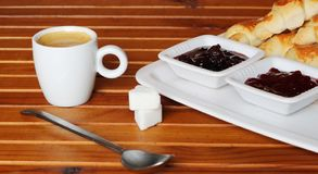 Croissant, cherry marmalade and orange and a cup of coffee on a plate on wooden table stock photography