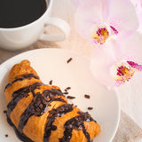 Croissant with chocolate, cup of coffee and a pink orchid. Roman Royalty Free Stock Photo