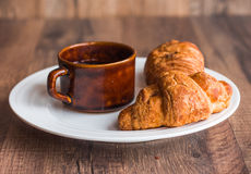 Croissant with chocolate on a white plate, a cup of coffee Royalty Free Stock Images